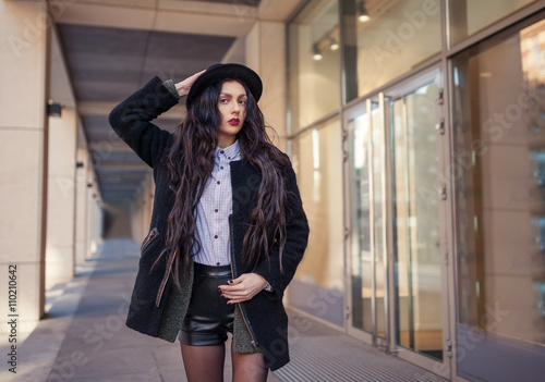 Outdoor lifestyle portrait of pretty young girl, wearing hipster swag  grunge style on urban background. Wearing hat and jeans denim. Spring  fashion woman.