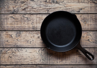 Traditional cast iron skillet pan on vintage wooden table background. Kitchen equipment