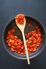 Oven roasted cherry tomatoes in frying pan. Selective focus on the wooden spoon.