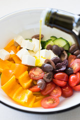 Olive oil being poured into bowl with ingredients for greek salad. Selective focus.