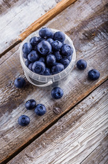Blueberries in a plastic can on old rustic white wooden table