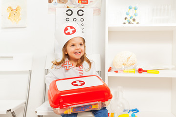 Girl dressed like doctor with toy first-aid chest