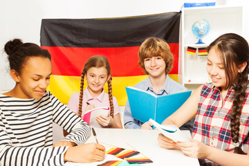 Four multiethnic students studying German at class