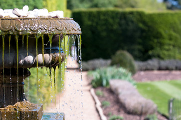 Cool water flowing from an old antique fountain
