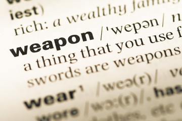 Close up of old English dictionary page with word weapon