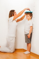 Mother measuring her son's height against wall