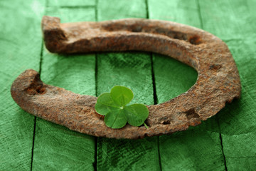 Wall Mural - St. Patricks day, old horse shoe with clover leaf on green wooden background
