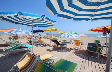 shade of the umbrellas on the beach of the tourist village by th