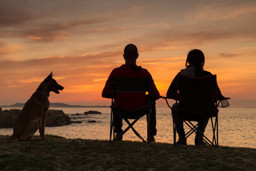 Couple and dog sitting at sunset at the beach
