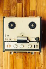 Antiguo grabador de cinta abierta sobre piso de madera