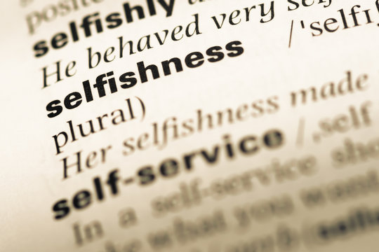 Close up of old English dictionary page with word selfishness