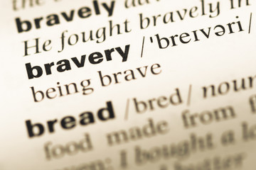 Close up of old English dictionary page with word bravery