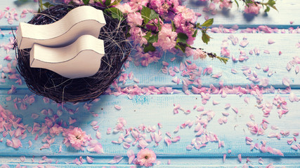 Pink  sakura flowers and two white wooden decorative birds in ne