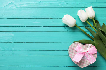 Background with white tulip flowers and gift box in form of hear