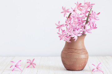hyacinths in vase on white wooden planks