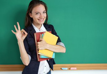 Happy smiling student showing okay gesture. Photo of teen near blackboard, education concept