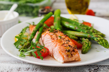 In de dag Vis Baked salmon garnished with asparagus and tomatoes with herbs
