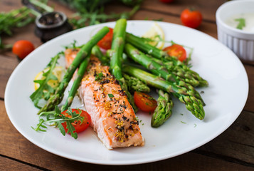 Foto op Textielframe Vis Baked salmon garnished with asparagus and tomatoes with herbs