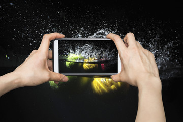 Taking pictures on mobile smart phone in Splashing fruit on wate