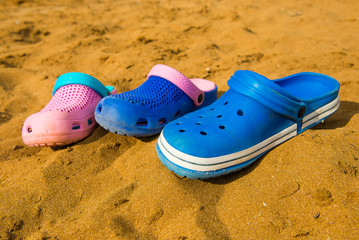 Crocs on the sand. three pairs of flip-flops on the beach, colorful beach shoes