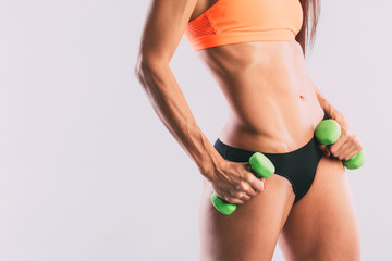 Athletic woman with dumbbells close-up.
