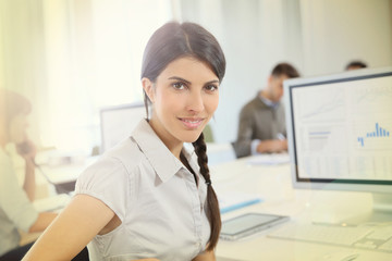 Portrait of young brunette woman working in office