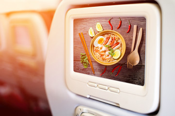 Aircraft monitor in front of passenger seat showing Thai food st