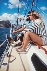 Young couple sitting together on yacht and looking at view