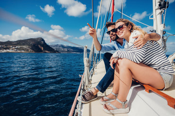 Young couple enjoying in summer day on yacht