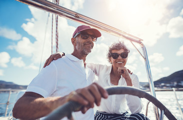 Happy mature couple at the wheel of a yacht