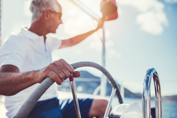 Senior man at the wheel of a yacht