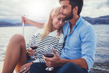 Young couple in love on sail boat with wine