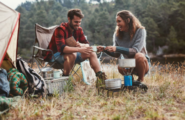Happy young couple camping by the lake