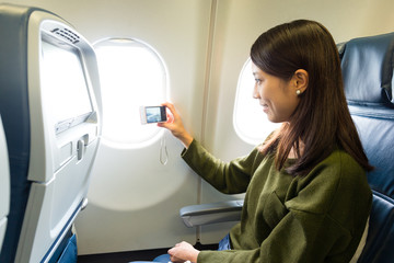 Woman taking photo on airplane