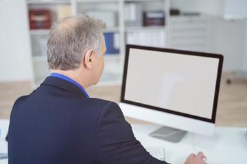 mann im büro schaut auf computer bildschirm