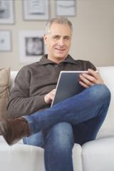 älterer mann sitzt auf dem sofa und liest am tablet