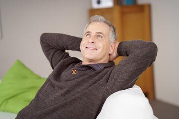 best ager sitzt auf dem sofa und schaut zufrieden nach oben