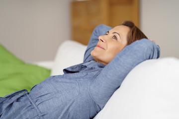 glückliche frau liegt entspannt auf dem sofa