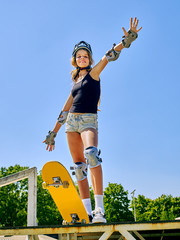 Portrait of teen girl hand up standing on his skateboard aganist blue sky outdoor.  Girl is preparing for difficult tricks on skateboard.