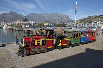 CAPE TOWN WATERFRONT SOUTH AFRICA - APRIL 2016 - Man in uniform carrying a red flag with a children's train ride around the harbor area of the V&A Waterfront. A major attraction in Cape Town