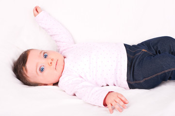Baby girl on white sofa.