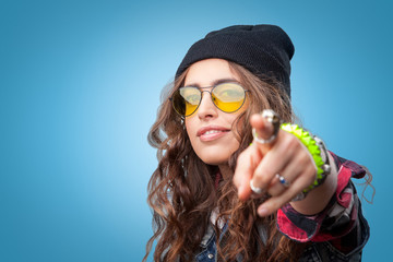 Closeup portrait of beautiful trendy hipster girl with long curly hair pointing finger at you and smiling wearing checkered shirt, black beanie hat and glasses on blue background.Youth style,fashion.