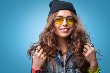 Closeup portrait of beautiful trendy hipster girl with long curly hair and hands up smiling wearing  checkered shirt, denim vest, black beanie hat and glasses on blue background.Youth style,fashion.