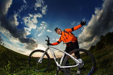 biker in orange jersey riding on green summer field