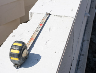 Yellow tape measure on white concrete blocks. Construction site concept