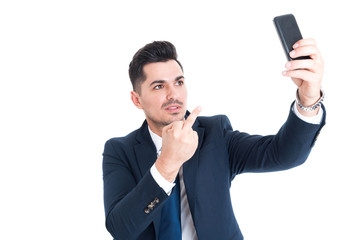 Businessman taking a selfie and showing middle finger