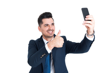 Happy businessman making a selfie and showing thumb up