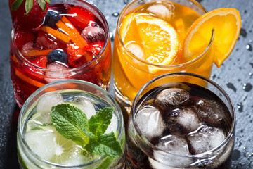 assortment of fresh iced fruit drinks on a dark background