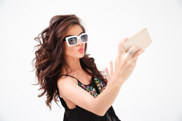 Fashion woman in sunglasses making selfie photo on smartphone