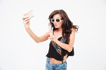 Woman making selfie photo and showing peace sign